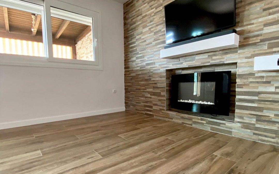 Resultado de reforma de salón con materiales elegidos con el cliente. integrando el televisor y la chimenea para crear un ambiente acogedor y muy personal